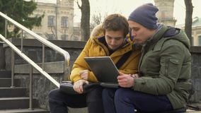 Two guys with laptop at park. Two students sits in the park and discuss something looking on laptop. Friends talks with each other and have a conversation about stock video footage