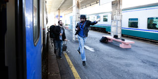 Two guys are late for the train and running to catch it. One of them is wasted. Royalty Free Stock Photography