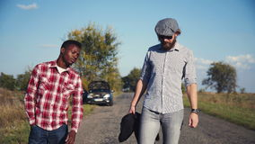 Two guys left broken car and hitchhiking. stock footage