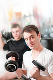 Two guys lifting heavy dumbbells Royalty Free Stock Photo