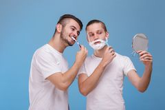 Two guys look into mirror. One of them brushes his teeth , and the second shaves beard. Two young guys of European appearance look into one small round mirror Stock Image