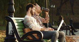 Two guys with nootbok talking in the outside on the chair in sunlight. Red Epic 4k. Two guys with nootbok talking in the outside on the chair in sunlight stock footage
