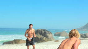 Two guys passing the football to one another. While palying near the sea stock video