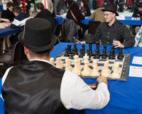 Two guys play chess at Festival del Fumetto convention in Milan, Italy. MILAN, ITALY - FEBRUARY 2: Two guys play chess at Festival del Fumetto, convention Stock Images