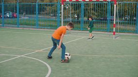 Two guys play football in the playground