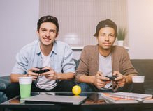 Two guys playing on the console sitting on the couch Royalty Free Stock Photography