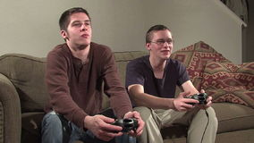 Two guys playing games. 2 guys playing video games. On a couch stock video