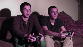 Two guys playing games. 2 guys playing video games. Lit by TV screen stock footage