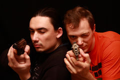 Two guys playing with gun Stock Photo