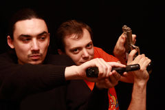 Two guys playing with gun Stock Image