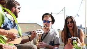 Two guys playing music at the party while girl taking photos and laughing. Two charismatic guys playing music with guitar and saxophone at the party while girl stock footage