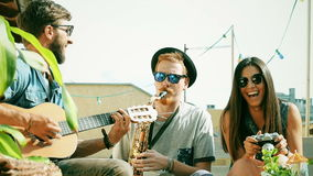 Two guys playing music at the party while girl taking photos and laughing. Two charismatic guys playing music with guitar and saxophone at the party while girl stock video footage