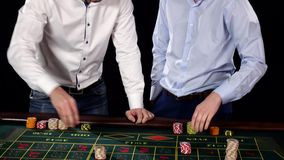 Two guys playing roulette in the casino. Black. Two guys playing roulette in the casino, white shirt, blue shirt cute funny guys, cam moves top down then cam stock footage