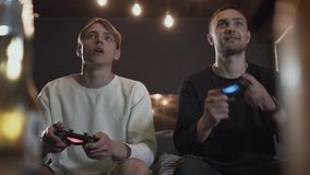 Portrait two guys playing video game in the gaming room sitting on the sofa. Friends fighting using joysticks. Friends. Two guys playing the video game in the stock footage