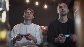 Two happy guys playing video game in the gaming room sitting on the sofa. Friends spending time together indoors. Video. Two guys playing the video game in the stock video