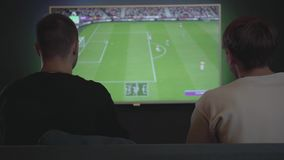 Two guys playing video game in the gaming room sitting on the sofa indoors. Friends playing football. Friends spending. Two guys playing video game in the gaming stock footage