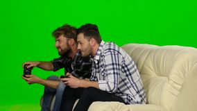 Two guys playing video games with wireless control pad. Green screen. Two guys playing video games with wireless control pad, men sit on the couch and control stock footage