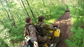 Two guys on quad ride through the forest. Two guys on yellow quad ride through the forest stock video