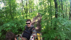 Two guys on quad ride through the forest. Two guys on yellow quad ride through the forest stock video footage
