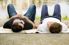 Two guys relaxing alongside a river. Two guys relaxing together lying in their jeans on a blanket alongside a river or lake Royalty Free Stock Photo