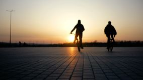 Two guys ride on bicycles towards the sunset on a large area. Silhouettes people against the background of the sun. Sunlight stock video footage