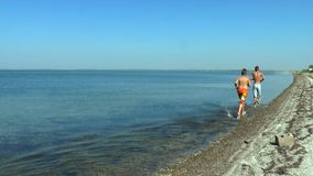 Two guys run along the seashore. Against the background of the blue sky and the sea stock footage