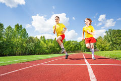 Two guys running together in competition. On stadium road royalty free stock photo