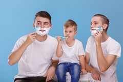 Two guys shave a beard, and a little boy brushes his teeth. On a blue background. Two young guys of European appearance shave a beard with a disposable razor Royalty Free Stock Images