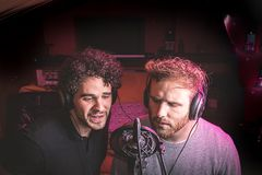 Two guys singing in a music studio royalty free stock images