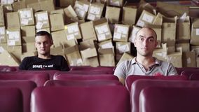 Two guys sit in raw of purple chairs with huge pile of boxes behind their backs.
