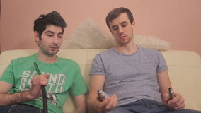 Two guys sitting on a couch and one showing off their electronic cigarettes. stock video