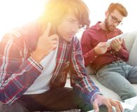 Two guys sitting on the couch, talking on the smartphone and communicating on the Internet. Modern lifestyle Royalty Free Stock Images