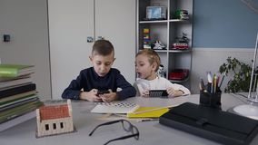 Two guys are sitting at the table in the white room and play an online game on their phones. Young caucasian child. Playing online games on smartphone slow stock video footage