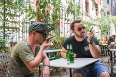 Two guys are smoking cigars and drinking beers royalty free stock images