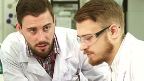 Close-up of the faces of the laboratory technicians who conduct a serious conversation. Two guys stand next to each other on the laboratory. Close-up shows their stock video