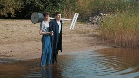 Two guys stand in water shore looking down, talking and start shout summer day. Two guys stand in water shore looking down, talking and start shouting on a stock footage