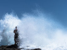 Two guys standing on a rock in the waves. Stock Photography
