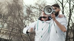 20s rebels scream in a loudspeaker on a revolution on a street in the city. Two guys on strike shouting into a megaphone close-up. People are yelling on the stock footage