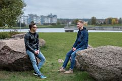 Two students sitting and talking, city landscapes and buildings in the background. Two guys students sitting and talking, city landscapes and buildings in the Royalty Free Stock Photography