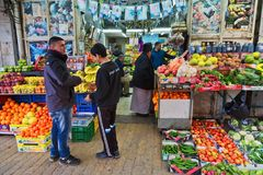 Two guys are talking near small shop in Jerusalem. JERUSALEM, ISRAEL - DECEMBER 29, 2016:Two guys are talking near small shop with fruits and vegetables in Royalty Free Stock Photography