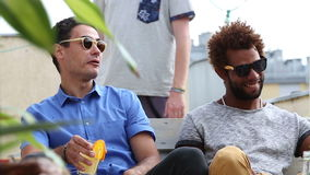 Two guys talking at rooftop party stock footage