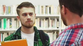 Two serious young men talk about something. Two guys are talking. They stand in the center of the library opposite each other. They look very serious. The man stock footage
