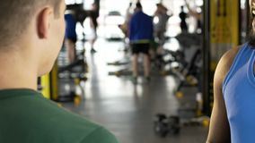Two guys talking to each other in gym, international communication, friends. Stock footage stock video footage