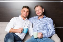 Love and relationships. Two happy guys together on couch stock photo