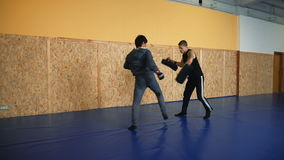 Two guys are training mixed martial arts in the hall fighting arts stock video