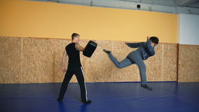 Two guys are training mixed martial arts in the hall fighting arts. Practice melee combat in the martial arts hall stock video footage