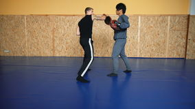 Two guys are training mixed martial arts in the hall fighting arts. Practice melee combat in the martial arts hall stock video
