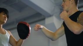 Two guys are training mixed martial arts in the hall fighting arts. Practice melee combat in the martial arts hall stock footage
