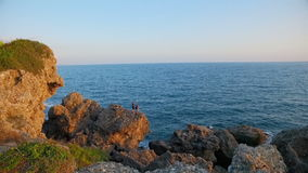 Two guys traveler standing on the rocks the coast. Two guys traveler standing on the rocks of the coast and enjoy the beautiful view of the sea and sunset stock video footage