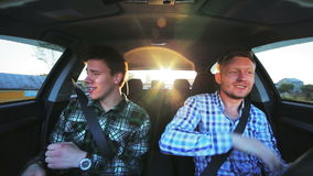 Two guys travelling in a car, fast driving, dancing, singing, smiling. In full HD stock footage